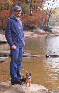 Image of man with small dog at river